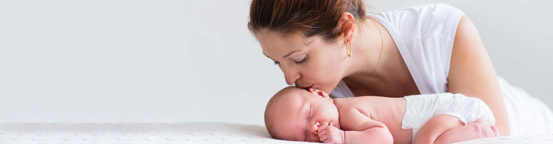 Woman kissing her newborn baby.