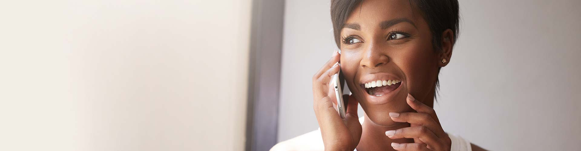 Young attractive African woman with short haircut talking on cell phone.
